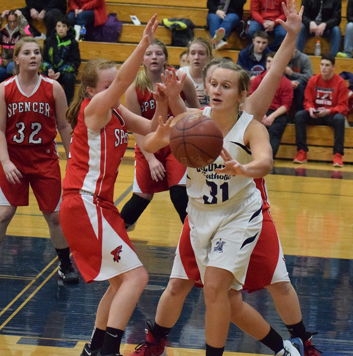 Columbus Catholic's Marissa Immerfall passes the ball out of traffic as she is surrounded by the Spencer defense during a game Dec. 11 at Columbus Catholic High School. Paul Lecker photo